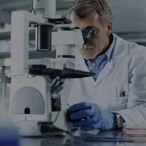 Homme qui regarde dans microscope en laboratoire